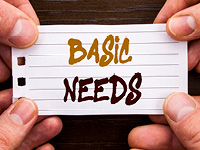 "Four Hands hold a note with the words ""basic needs"""
